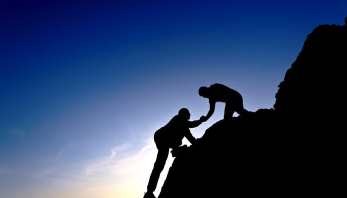 Silhouette of helping hand between two climbers